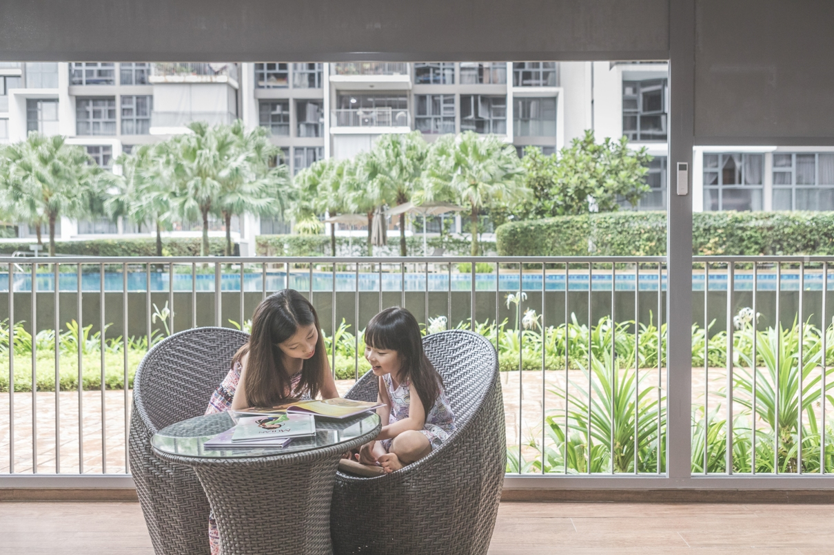 Two girls reading a book beside the ALTEX SecureZIP outdoor blinds