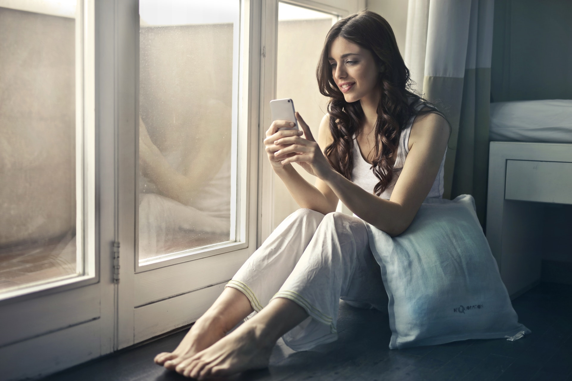 A young lady uses her smartphone at home