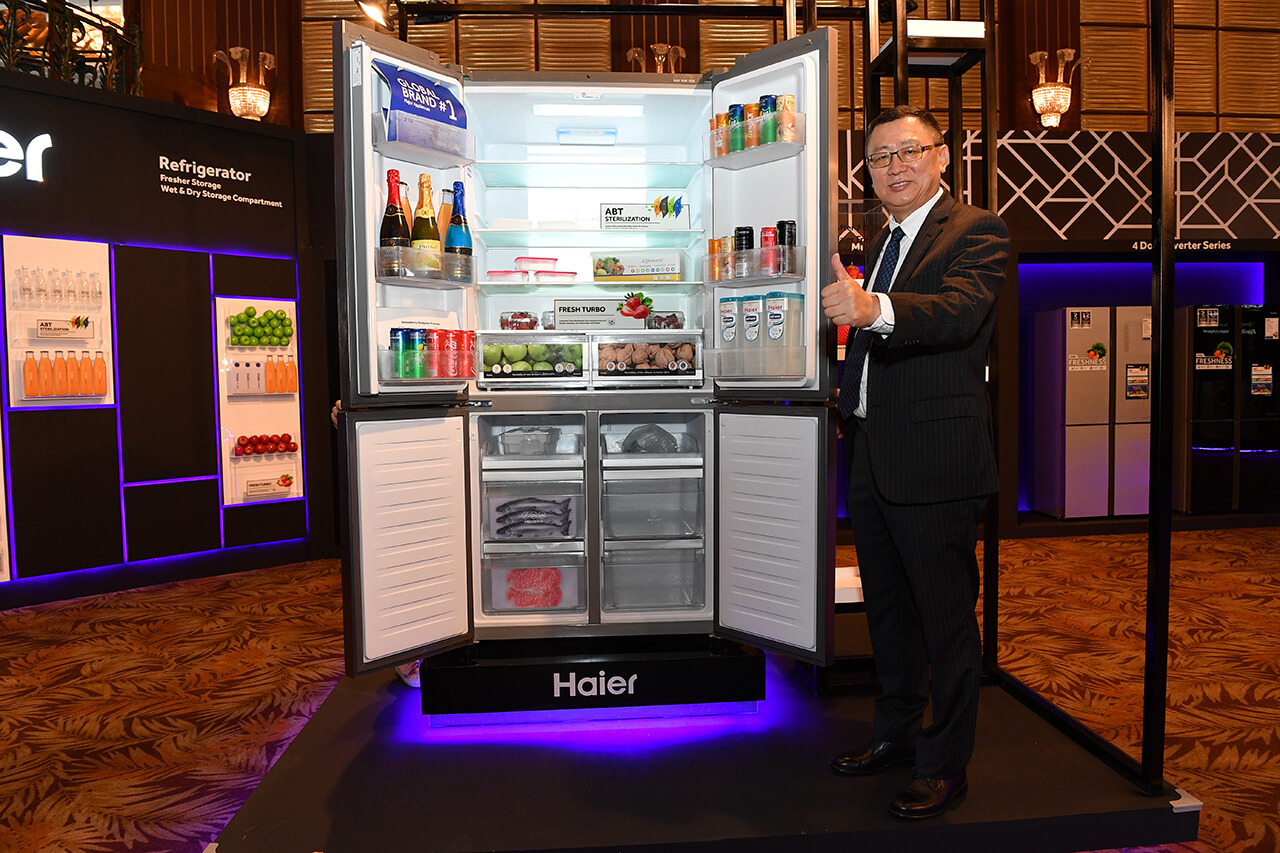 Shi Zhiyuan posing with the new Haier 4-Door Series inverter refrigerator